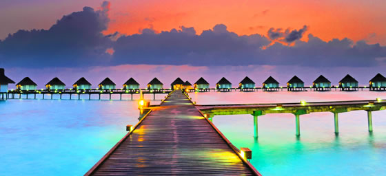 A view of overwater bungalows in the Maldives at dusk, which can be enjoyed with a cheap flight from Flight Centre.